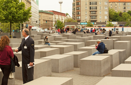 gravestones: Germany-Berlin, May 2016. Memorial for the Murdered Jews of Europe.Guide Provides tourism information and people sitting on the stone blocks symbolizing the gravestones. Editorial.Horizontal view.