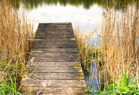blemishes: Photo closeup of a wooden pier on the lake. Clearly visible boards and blemishes on wood. Horizontal view. Stock Photo