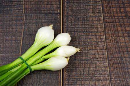 buch: Fresh buch of spring onions on wooden background with empty space for text on the right,,flat top view.Horiontal.