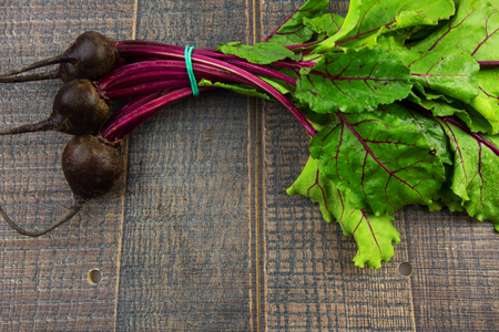 tex: A bunch of fresh young beets with green beetroot on wooden background with empty space for tex at the bottom. Flat top view.Horizontal.