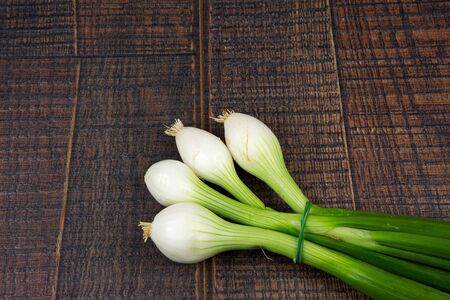 buch: Fresh buch of spring onions on wooden background with empty space for text on the left,flat top view.Horiontal. Stock Photo