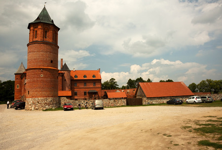right bank: View of gothic castle in Tykocin located on the right bank of Narew river, Poland in beautiful sunny summer day. Editorial.Horizontal view.