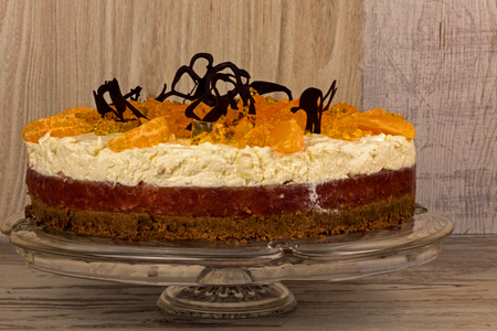 Fresh orange cake layered with mascarpone cheese, jelly, orange particles and foster bitter chocolate, stands on the plate on an old wooden table. Close, horizontal view from the side. Reklamní fotografie