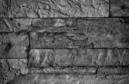Interesting black and white stone wall with visible scratches and grain.Close,horizontal view.