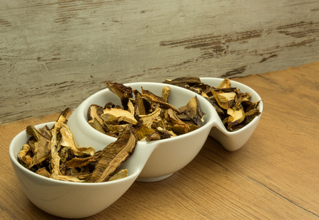 Dried, aromatic forest mushrooms in a white bowl on a wooden kitchen table. Perfect for soups and various dishes. Horizontal view.