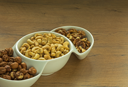 Hazelnuts, Italian and Cashew Nuts in a white three-piece bowl, on a wooden vintage kitchen table. Healthy food.Close, horizontal view. Reklamní fotografie