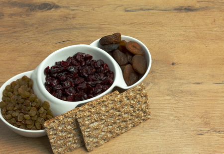Dried apricots, cranberries, raisins and two pieces of crisp bread on an old,wooden, kitchen table. Close, horizontal view. Reklamní fotografie