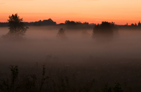 The rising sun illuminates the morning fog hanging over the meadow, in the distance you can see the outlines of the houses. Beautiful, interesting and mysterious landscape, illustration .Poland in May. Horizontal view Reklamní fotografie