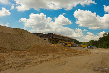 Construction site of a highway leading through the forest with visible sand, gravel and construction machinery under blue sky with white clouds. Poland in summer. Horizontal view.
