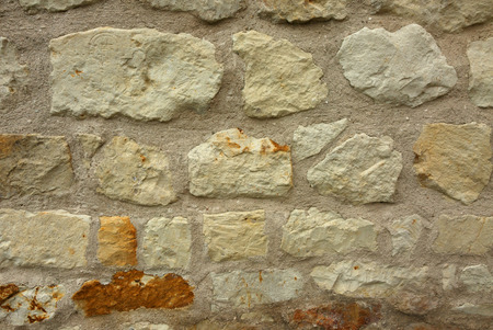 Old, porous stone wall as a very interesting background and texture. Horizontal view.