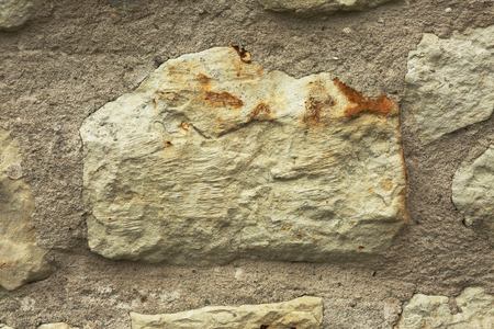Close up of a large stone in an old historic wall with visible details and porosity and bright mortar around. Horizontal background, texture