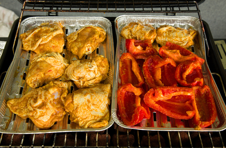 Chicken legs in spices and pieces of red peppers on the trays fry them on the grill.Close,horizontal view.