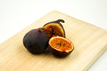 Two fresh figs, one cut in half with visible pulp, on kitchen board and white background .Close, horizontal view