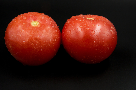 Two fresh red watered tomatoes with clearly visible droplets isolated on black background.Close, horizontal view