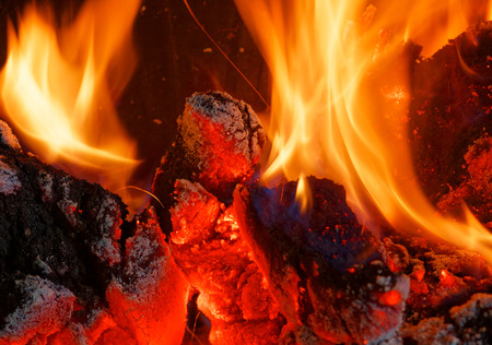 Closeup of glowing coals and wood in a fireplace. Interesting, abstract background, texture.