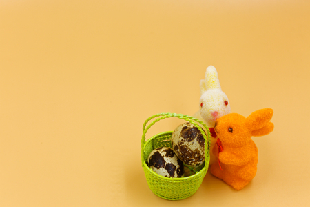 Two colorful Easter bunnies and a green basket with eggs on an orange background, easter decoration.Horizontal view. Reklamní fotografie
