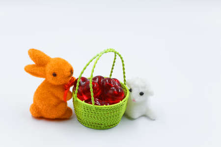 Orange bunny and white Easter lamb next to a basket with eggs isolated on a white background.Horizontal view.