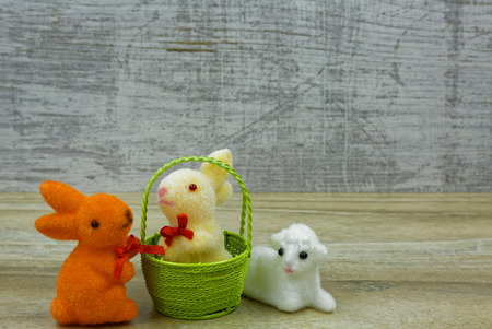 Two easter bunnies and lamb as easter decoration on a wooden background.Horizontal view.