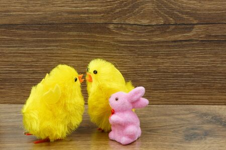 Two yellow chickens and a pink bunny on an old wooden counter. An interesting Easter decoration.Horizontal view. Reklamní fotografie