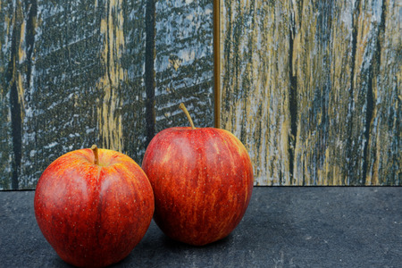 Two, fresh red apples on an old stone kitchen counter in vintage style. Horizontal view
