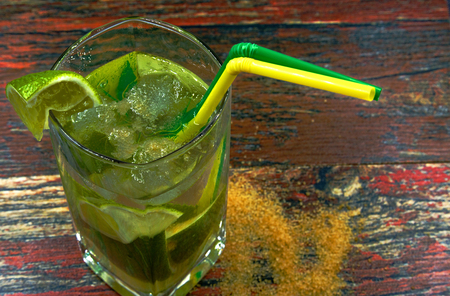 Glass of fresh Caipirinha drink with ice and lemon on wooden , vintage backround.Close , horizontal view from above