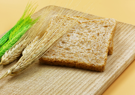 Several ears of cereal and slices of bread on an old wooden board.Close horizontl view.