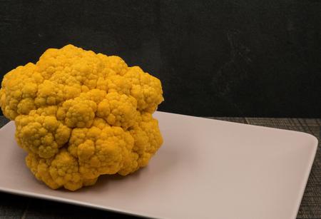 Closeup photo of a yellow cauliflower arranged on a light pink dish. Horizontal view.