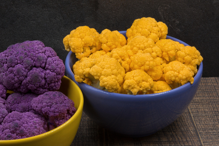 Shredded yellow and purple cauliflower in viole and yellow bowls.Close,horizontal  view. Stok Fotoğraf