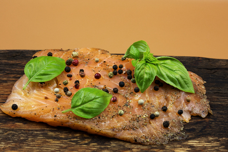 Photo of a piece of smoked salmon, garnished with colorful peppercorns and basil leaves, arranged on an old wooden chopping board with copy space on the top.Horizontal view from above.