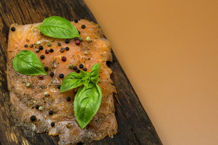 Photo of a piece of smoked salmon, garnished with colorful peppercorns and basil leaves, arranged on an old wooden chopping board with copy space on the right side.Horizontal view from above. Reklamní fotografie - 104422702