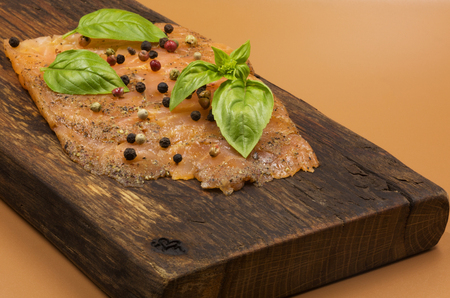 Close view from above on the smoked salmon sprinkled with colorful pepper and garnished with basil leaves.The whole stacked on an old wooden chopping board in vintage style. Reklamní fotografie - 104422704