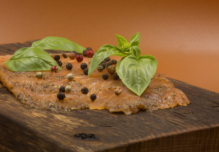 Close view from low perspective of smoked salmon sprinkled with seeds of colored pepper and garnished with freshly basil leaves.Concrete on an old wooden chopping board in vintage style