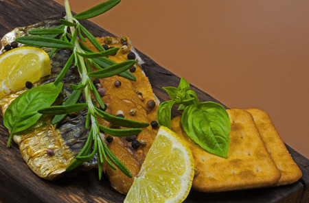 Two pieces of smoked mackerel sprinkled with colorful pepper, garnished with lemon, a fresh sprig of rosemary and basil leaves, on an old wooden board in vintage style.Close,horizontal view from above.