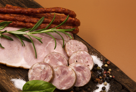A set of cold cuts, dry sausages, slices of ham and pork sausages arranged on an old wooden board and garnished with colored pepper, salt, rosemary twig and basil leaves. Vintage style.Close, horizontal view.