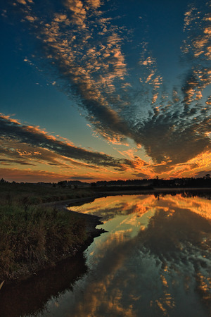 Beautifully highlighted in red and yellow clouds with a dawn over the lake. Intresting and mysterious landscape with the reflection of the clouds in the water. Mazury district in Poland, september.Vertical view. Stok Fotoğraf