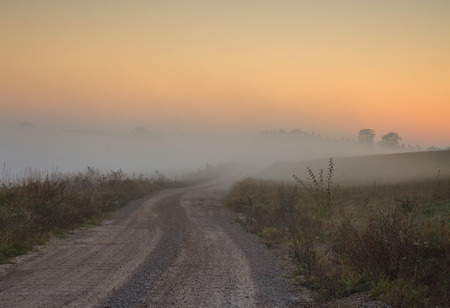 Landscape with a dirt road among meadows, disappearing in the dense fog beautifully highlighted by the rising sun on a background of blue sky covered with fog. October, autumn in Poland. Stok Fotoğraf