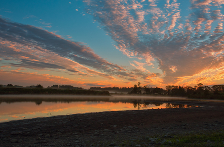 Highlighted in red, pink and yellow clouds at sunrise, their reflection in water and delicate fog. Beautiful, mystical, October morning at the lake. Poland, Mazury district in the autumn. Horizontal view.