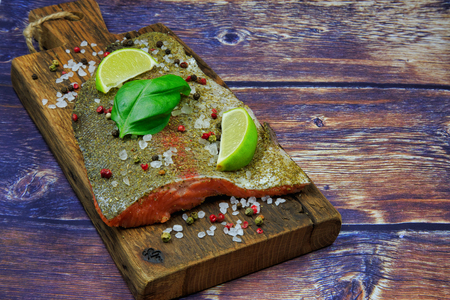 Raw rainbow trout steak sprinkled with spices, pepper, salt with pieces of lime and basil leaves on an old wooden board. Flat view from above in vintage style.Horizontal view Stok Fotoğraf