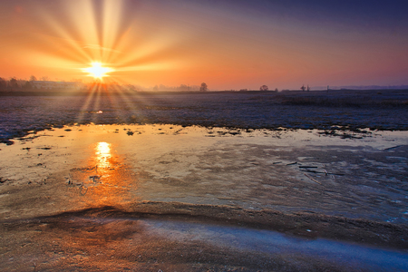Sunrise over frozen fields and the reflection of the sun in the ice covering the field.Polska at the end of February.Horizontal view.