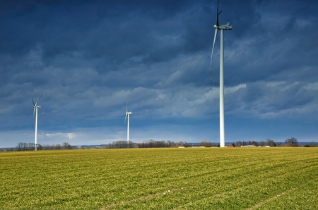 Three windmills for electric power production surrounded by agricultural fields in Polish country side., against the background of heavy, black clouds.Horizontal view.