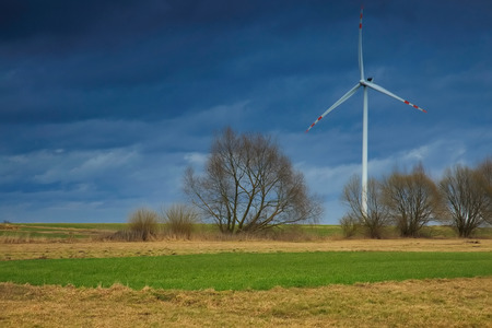 One windmill for electric power production surrounded by agricultural fields in Polish country side., against the background of heavy, black clouds.Horizontal view.