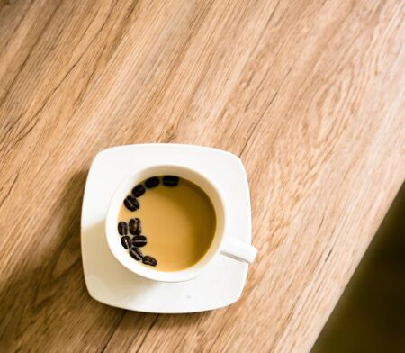 Coffee cup with milk on the wooden table Reklamní fotografie - 150124938