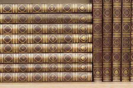 encyclopedias: Enciclopedias en orden alfab�tico de pie sobre una plataforma de madera