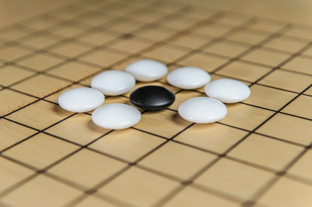Ancient strategy game with stones and bamboo board Banco de Imagens