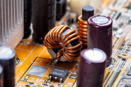 Copper coil, inductor winding part on a pc motherboard, circuit board macro, closeup. Coil whine noise issue abstract concept, electronic element detail, computer electronics, visible uncovered coil Reklamní fotografie
