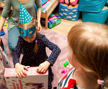 Cracow, Malopolska / Poland - November 20 2019: Young birthday girl with a blue party hat and a mask unpacking her birthday present, her jealous little sister watching Siblings jealousy simple concept