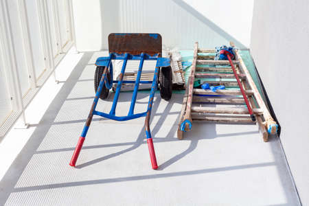 Handtruck and a wooden painter ladder and a mop laying on the white balcony. House or flat under construction abstract concept. Construction or painting crew tools and equipment, stepladder, nobody