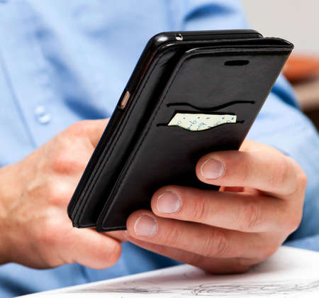 Man in a blue shirt checking his phone, social media, holding it in hand tapping the screen with his finger. Phone in leather stylish openable case, note paper attached. Square composition, front view