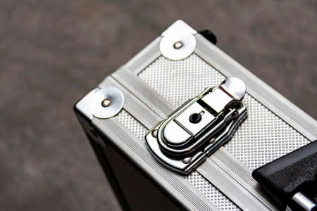 Silver metal suitcase, box, crate or simple case with a handle for equipment, valuables or money secure transport closeup. Safe storage abstract concept. Focus on the briefcase lock clip mechanism