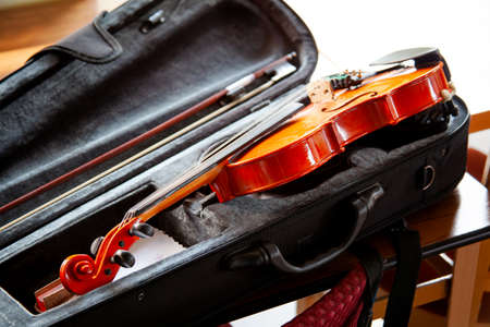 Violin with a bow laying in an open black fiddle case on the table. Classical musical string instruments group concept, nobody. Safe instrument storage for travelling Stock Photo